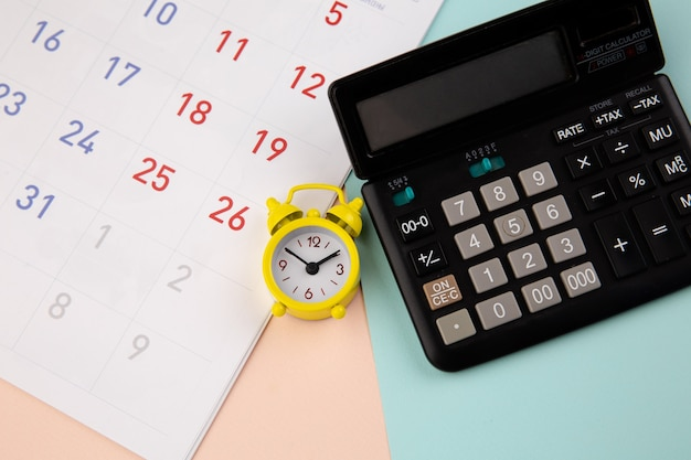 Sveglia, calcolatrice e calendario - concetto di tempo aziendale o fiscale.