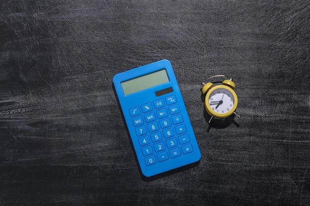 Sveglia e calcolatrice sulla lavagna della scuola. di nuovo a scuola Foto Premium