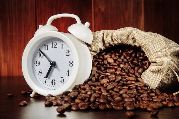 Sveglia e chicchi di caffè in un primo piano del sacco.