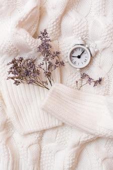Sveglia e fiori secchi su un accogliente maglione bianco. concetto di tempo di benessere. vista dall'alto e verticale