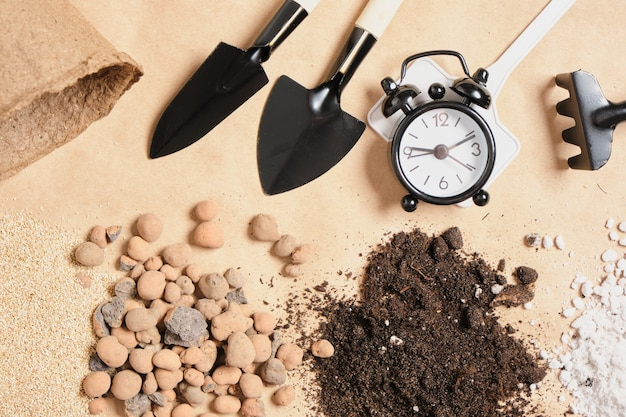 Sveglia, articoli da giardinaggio, additivi per il suolo e fertilizzanti su carta kraft, luogo di copia, concetto di giardinaggio, tempo di piantare semi