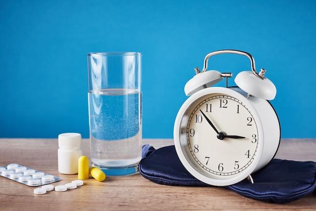Sveglia, bicchiere d'acqua, tappi per le orecchie e pillole su sfondo blu