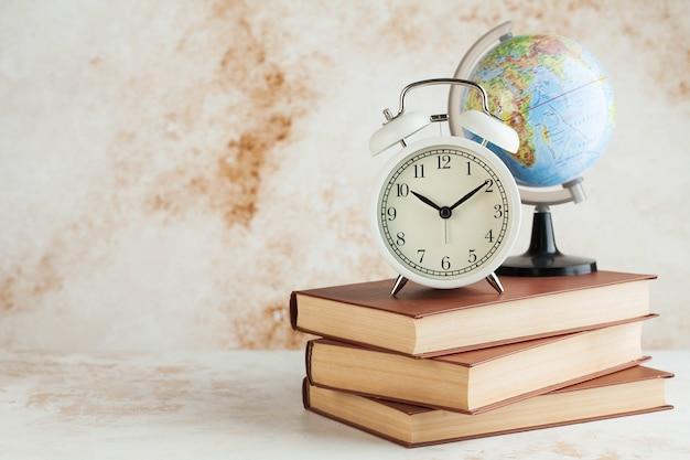 Sveglia e globo sui libri. il concetto di iniziare la scuola, tempo di viaggio. copia spazio.
