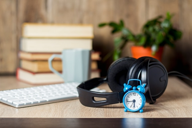 Sveglia, cuffie e tastiera sulla scrivania con i libri. concetto di ufficio, giornata di lavoro, retribuzione oraria, orario di lavoro, lavoro in un call center.