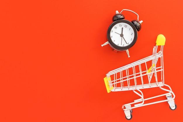 Sveglia e mini carrello su sfondo rosso. vendita, tempo di sconto, concetto di risparmio di tempo. vista dall'alto, piatto con spazio di copia.
