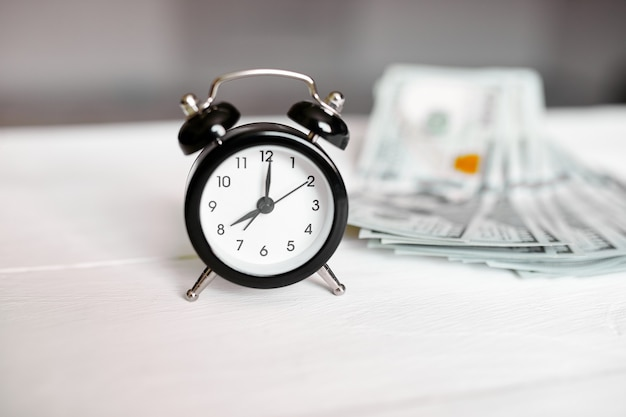 Sveglia e denaro su fondo di legno bianco, il tempo è denaro concept