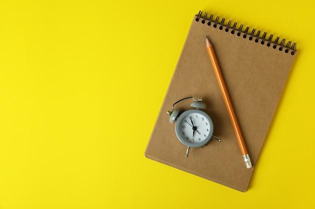 Sveglia, taccuino e matita su giallo