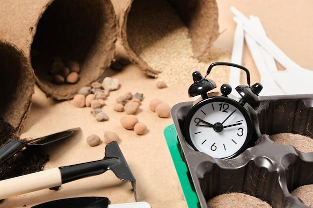 Sveglia e compresse di torba speciali per piantare semi, concetto di giardinaggio, semina primaverile, pale, piatti e terreno per piante