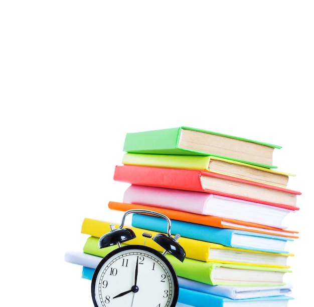 Sveglia e pila di libri su sfondo bianco