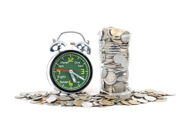 Sveglia che si leva in piedi con le monete isolate su priorità bassa bianca