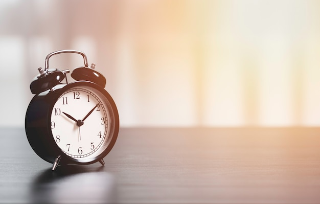 Sveglia sul tavolo per il concetto di tempo di investimento aziendale.