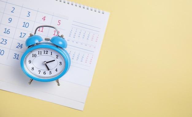 Sveglia con calendario su sfondo giallo.