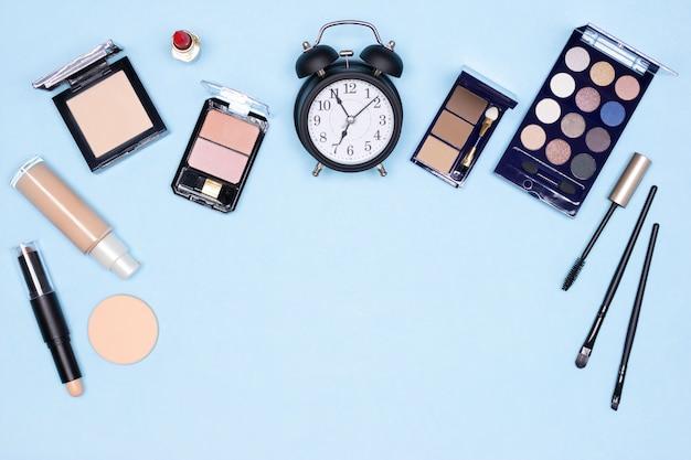 Sveglia con prodotti per il trucco essenziali concetto di trucco rapido di cinque minuti con spazio di copia