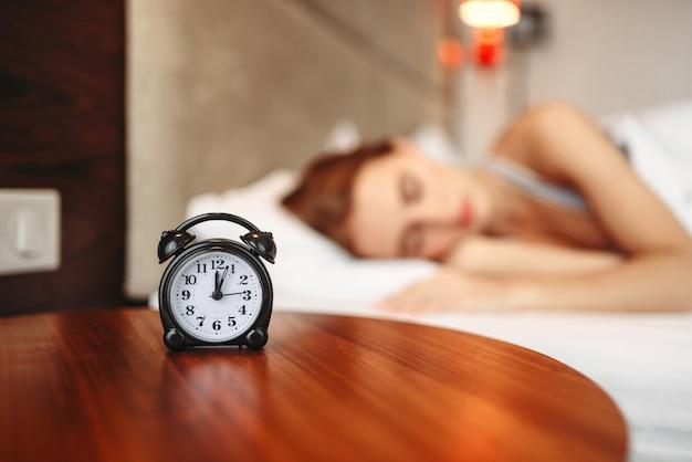 Sveglia, donna che copre le orecchie con cuscino