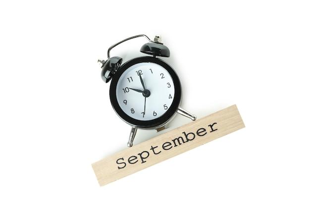 Sveglia e blocco di legno con testo settembre isolato su sfondo bianco