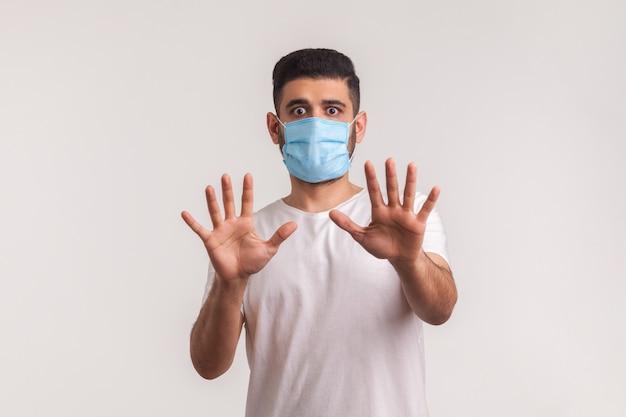 Uomo in preda al panico spaventato allarmante in maschera igienica che gesturing stop, paura dell'infezione da coronavirus