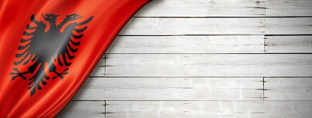 Bandiera dell'albania sul vecchio muro bianco. banner panoramico orizzontale.