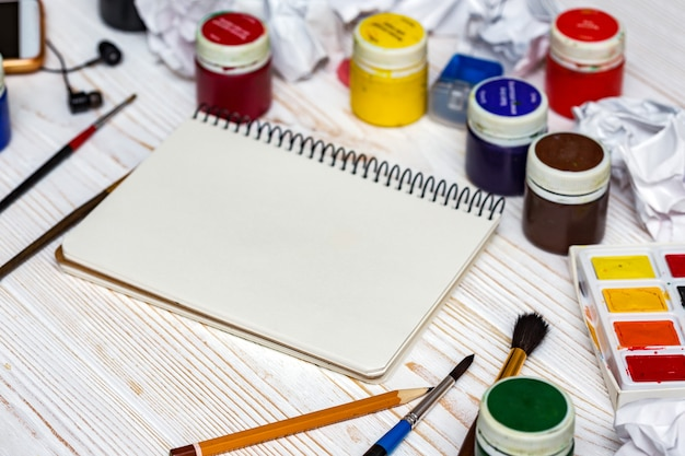 Pagine di album e vernici, matite, olio, pennello su fondo in legno