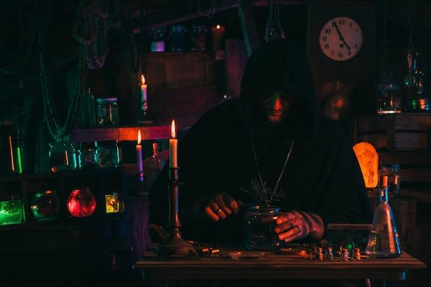 Il mago alchimista fa esperimenti con una pozione in un laboratorio con erbe e boccette di vetro