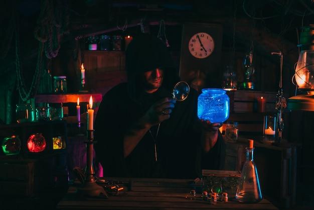 Il mago alchimista fa esperimenti con una pozione in un laboratorio