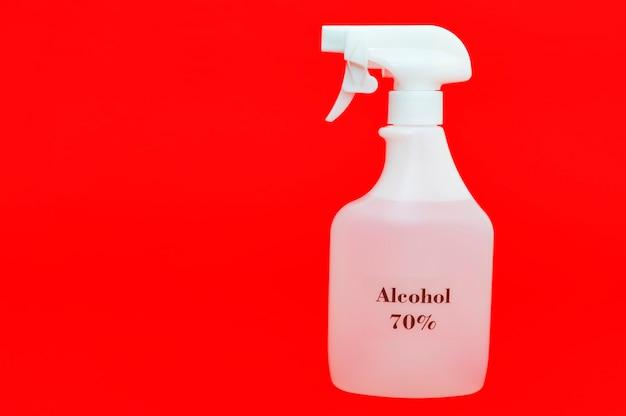 Alcool 70% spray per la protezione contro il coronavirus isolato su sfondo rosso