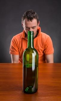 L'alcolista guarda la bottiglia di vino