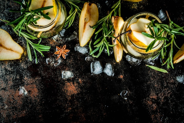 Bevanda alcolica, cocktail di pere dolci con rum, liquore, anice e rosmarino, su un nero arrugginito metallico, vista dall'alto