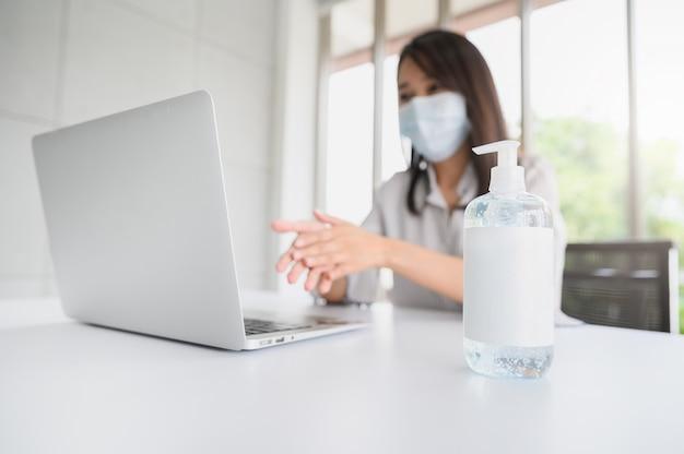 Bottiglia di gel di alcol con una donna che indossa la maschera facciale lavando la mano