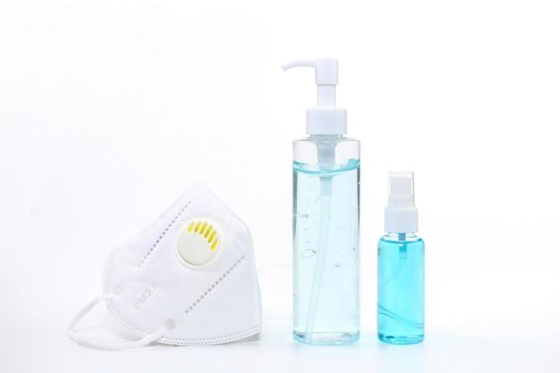 Gel alcolico, alcool spray e maschera facciale medica su sfondo bianco che sono respiratori
