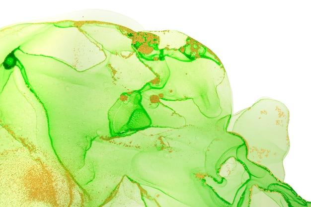 Inchiostro alcolico oro e macchie verde chiaro isolate su sfondo bianco