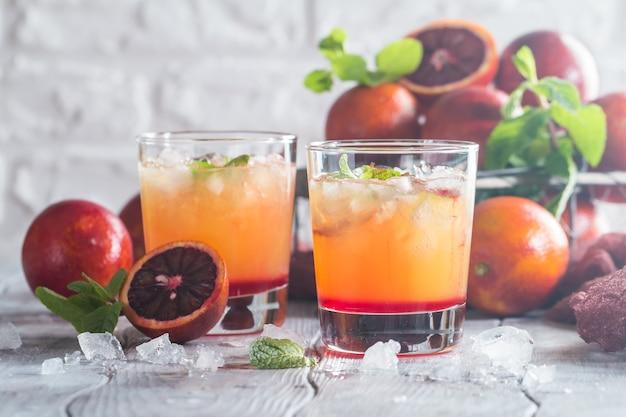 Cocktail di alba di tequila dell'alcool con ghiaccio e menta arancio rossi su bianco di legno