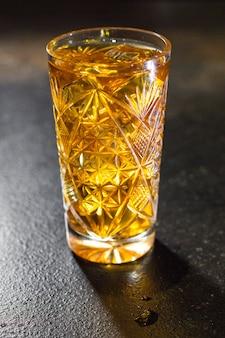Bevanda alcolica cocktail drink cubetto di ghiaccio limone e porzione di menta sul tavolo