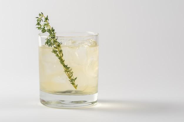 Cocktail alcolico decorato con timo in un bicchiere di vetro