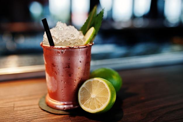Cocktail alcolico con ghiaccio e lime in bronzo può vetro sul tavolo del bar