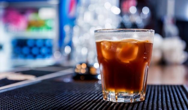 Cocktail alcolico con ghiaccio al bancone bar in legno. ristorante.