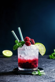 Cocktail alcolico con purea di rum o soda, lampone e mora, lime e menta nel bicchiere sul muro grigio scuro