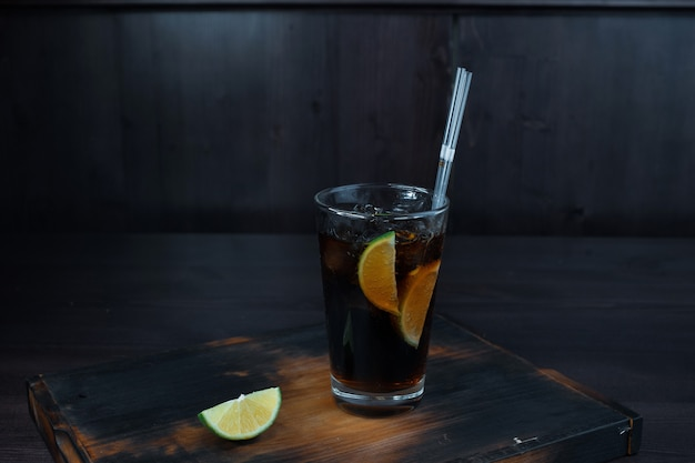 Gustoso cocktail alcolico con l'aggiunta di ghiaccio, whisky e coca-cola, fette di lime si trova su un tavolo di legno nel ristorante. la porzione originale di drink al bar.