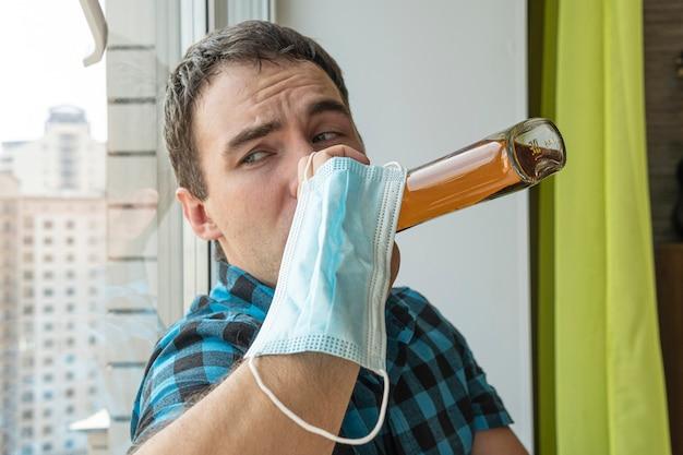 Alcolismo, dipendenza da alcol e concetto di persone - alcolizzato maschio con bottiglia di rum a casa. specialista disoccupato che si è ubriacato da solo per noia viene messo in quarantena in autoisolamento.