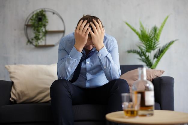 Alcolismo, depressione, crisi e concetto di fallimento - uomo d'affari depresso che beve alcolici a casa o in ufficio