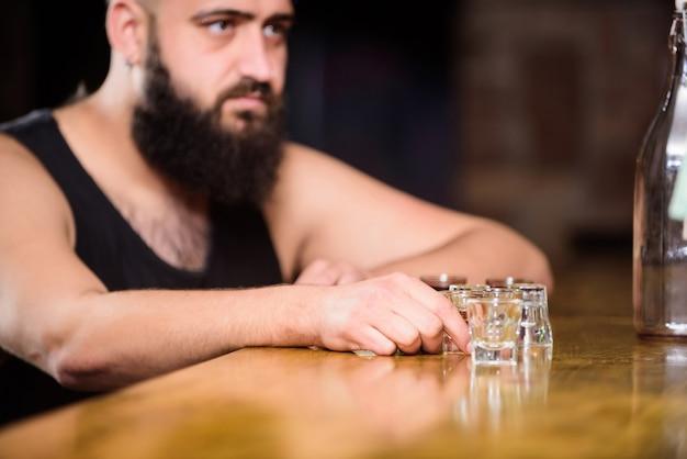 Alcolismo e depressione. il ragazzo trascorre il tempo libero al bar con l'alcol. l'uomo ubriaco si siede da solo in un pub. concetto di alcolismo. uomo brutale hipster che beve alcolici ordinando più drink al bancone del bar.