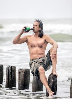 Alcolismo. uomo di mezza età con un torso nudo si siede su pali di legno sulla spiaggia e beve alcolici