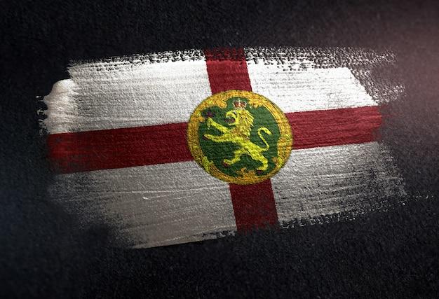 Bandiera di alderney fatta di vernice spazzola metallica sulla parete scura del grunge