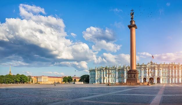 Colonna alessandrina con l'angelo vicino al palazzo d'inverno sulla piazza del palazzo a san pietroburgo e una nuvola bianca nel cielo blu