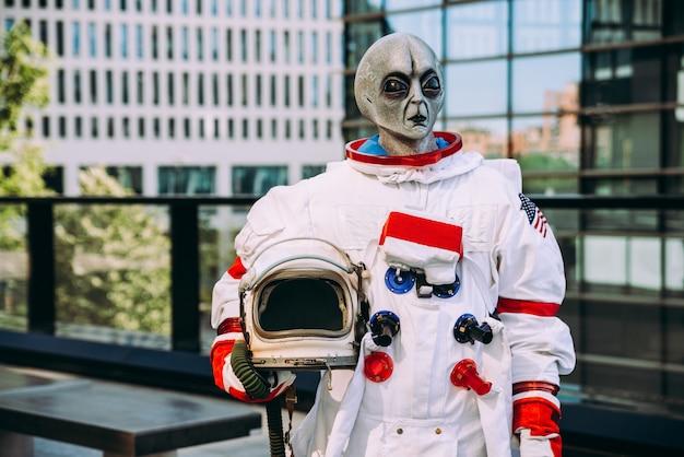 Astronauta alieno in una stazione futuristica. astronauta con tuta spaziale che cammina in un'area urbana
