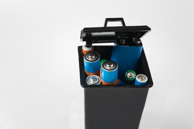 Batterie alcaline in contenitore di immondizia nero su superficie bianca. corretto smaltimento del concetto di batterie e accumulatori.