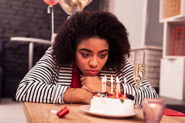 Tutto solo. bella donna afroamericana che guarda le candele pur essendo tutta sola per il suo compleanno