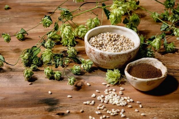 Tutto per la birra. coni di luppolo verde fresco, chicco di grano e malto rosso fermentato in ciotole di ceramica sul tavolo di legno.
