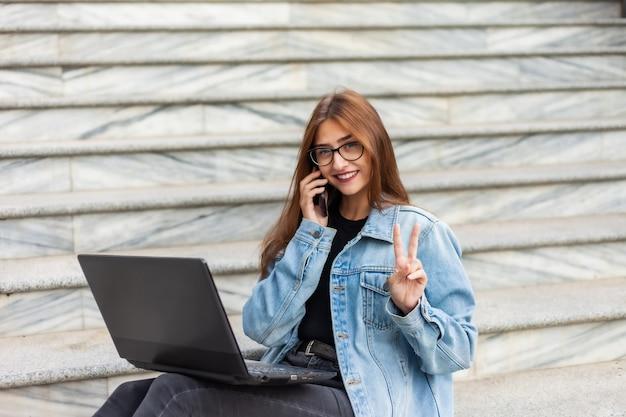 Tutti in affari. la giovane donna alla moda in una giacca di jeans e occhiali usa un computer portatile e parla al telefono mentre era seduto sulle scale in città. lavoro a distanza.