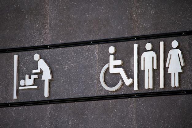 Tutti i sessi e segno di servizi igienici per disabili, segno di spogliatoio, design del segno minimo sul muro grigio, fuoco selettivo