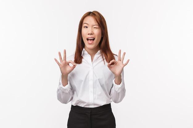 Va tutto bene. femmina asiatica soddisfatta e soddisfatta in camicia bianca formale, occhiolino e sorriso mostra gesto ok, niente di grave, dà sicurezza e garantisce una buona qualità del prodotto, niente di cui preoccuparsi